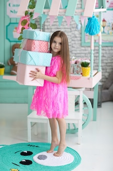 Pretty little girl in dress with presents