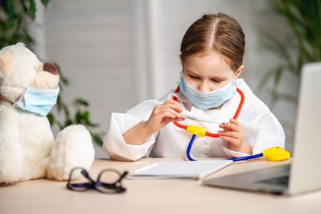 Хорошенькая маленькая девочка, одетая в белое лабораторное пальто и маску, измеряла температуру плюшевого мишки.