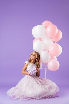 보라색 벽 위에 절연 앉아 공주 드레스를 입고 예쁜 소녀는 풍선과 선물 상자의 무리를 들고
