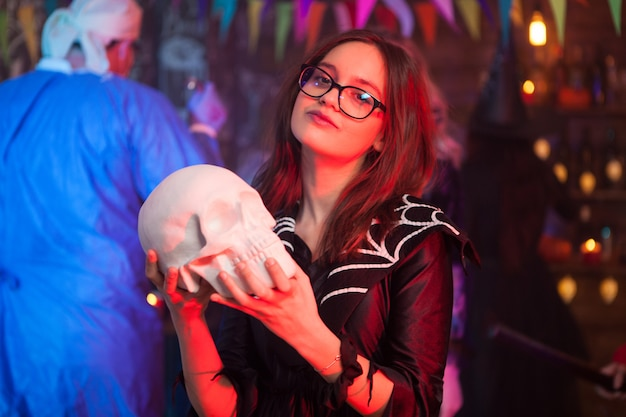 Pretty little girl dressed up like a witch holding a human skull at halloween party. creepy man dressed up like a doctor in the background.