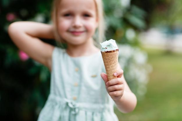 ワッフルコーンでなめる大きなアイスクリームを食べるかわいい女の子
