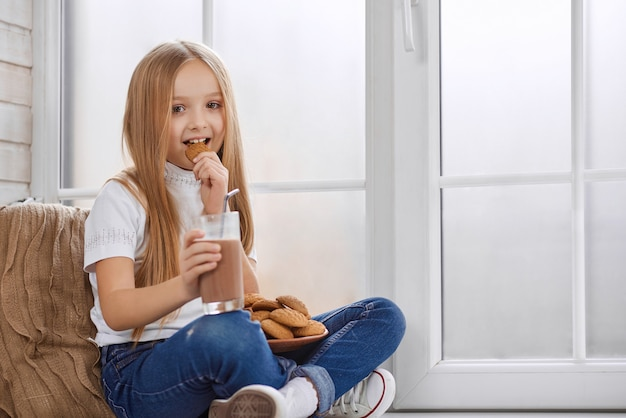 Pretty little girl eats cookies with chocolate milk