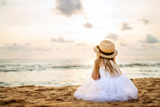 Pretty little girl from behind with long blonde hair in a straw hat and a white tutu dress sitting