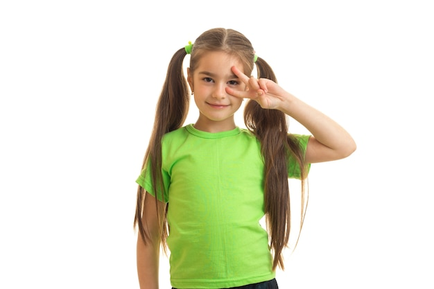 Pretty little girl in green t-shirt looks and poses on camera isolated on white background
