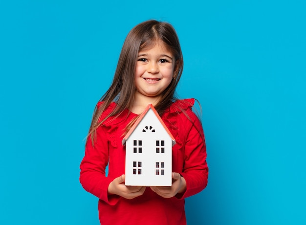 かわいい女の子の幸せな表情と家のモデルを保持しています