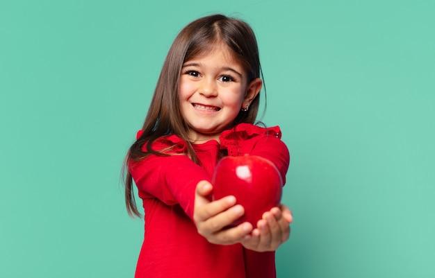 かわいい女の子の幸せな表情とリンゴを持っています