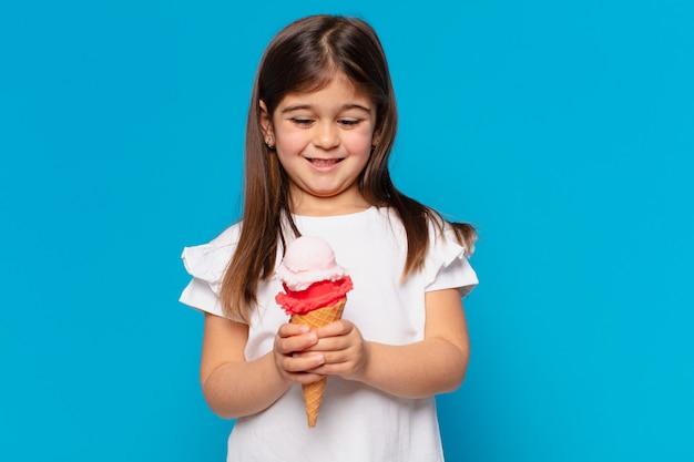 Красивая маленькая девочка счастливое выражение и держит мороженое