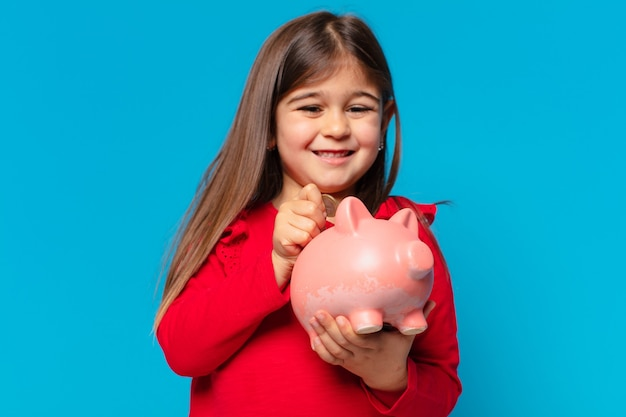 Pretty little girl happy expression and holding a piggy bank