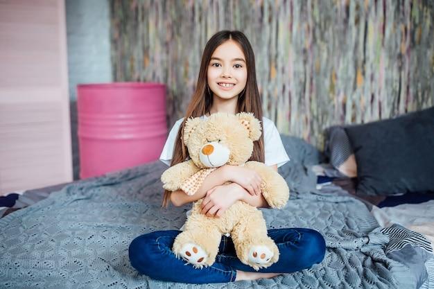 침실에 앉아있는 동안 곰을 들고 예쁜 소녀