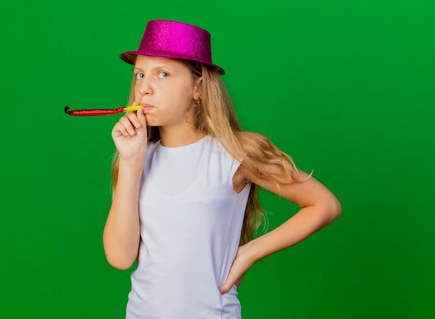 Bambina graziosa in cappello di vacanza che soffia fischio che celebra il compleanno