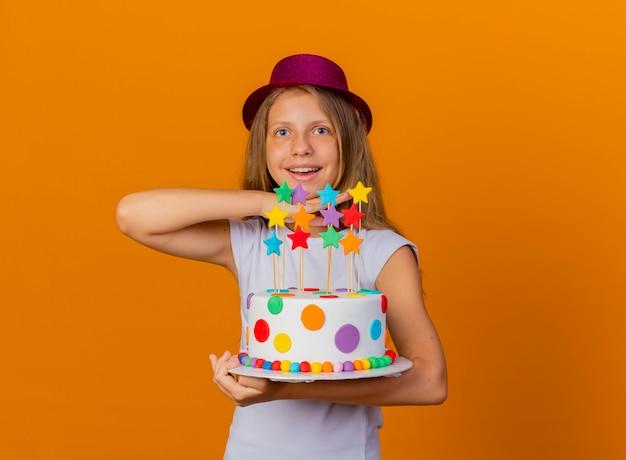 Bambina graziosa in cappello di festa che tiene torta di compleanno felice ed eccitata, concetto di festa di compleanno birthday