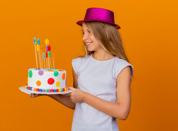 Pretty little girl in holiday hat holding birthday cake looking aside with smile on face, birthday party concept standing over orange background