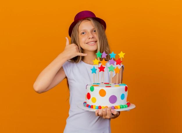 Bambina graziosa in cappello di festa che tiene la torta di compleanno che sorride facendo mi chiama gesto, concetto di festa di compleanno birthday