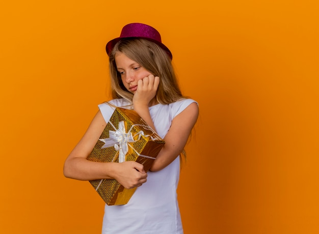 Pretty little girl in holiday hat holding gift box looking aside with pensive expression thinking, birthday party concept standing over orange background