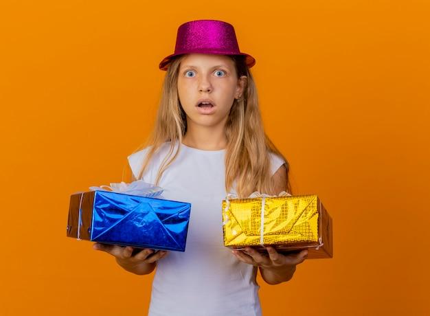 Bambina graziosa in cappello di festa che tiene i contenitori di regalo che guarda l'obbiettivo sorpreso e stupito, concetto di festa di compleanno in piedi su sfondo arancione