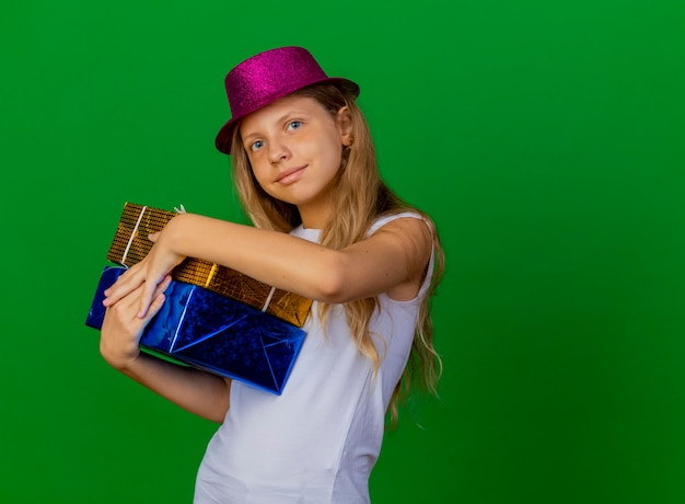 Pretty little girl in holiday hat holding gift boxes