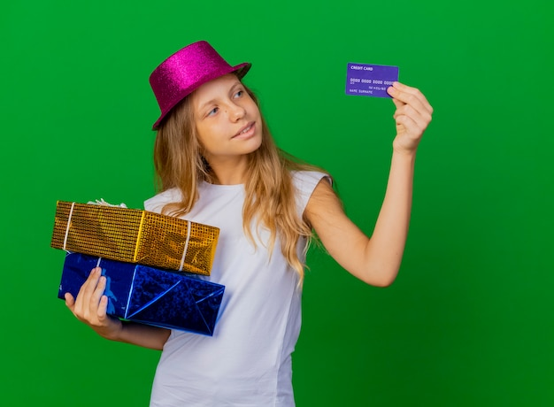 Bambina graziosa in cappello di festa che tiene i contenitori di regalo