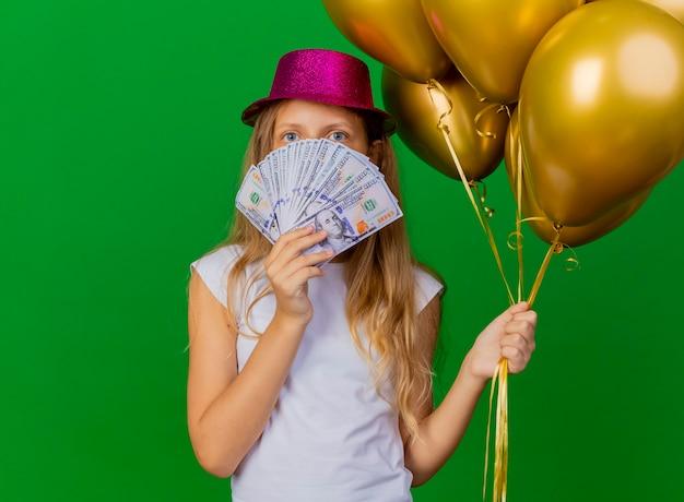 Bambina graziosa in cappello di festa che tiene soldi