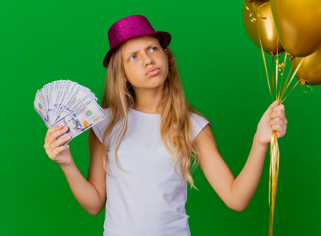 Pretty little girl in holiday hat holding money Free Photo