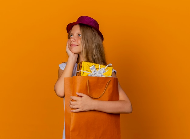 Pretty little girl in holiday hat holding paper bag with gifts looking aside with happy face, birthday party concept standing over orange background