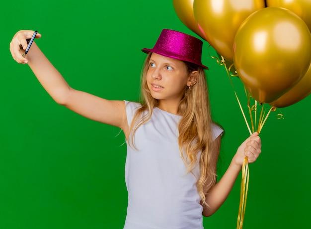 Bambina graziosa in cappello di vacanza che tiene smartphone