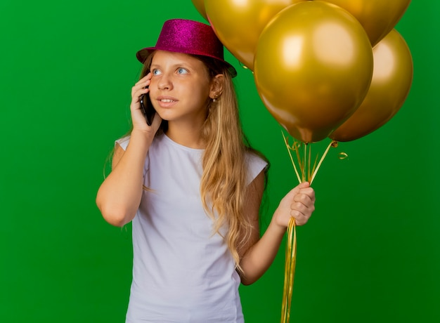 Pretty little girl in holiday hat holding smartphone