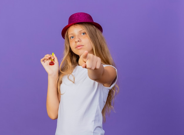 Pretty little girl in holiday hat pointing with index finger at camera with serious face, birthday party concept standing over purple background