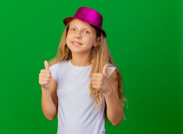 Bambina graziosa in cappello di festa sorridente che mostra i pollici in su