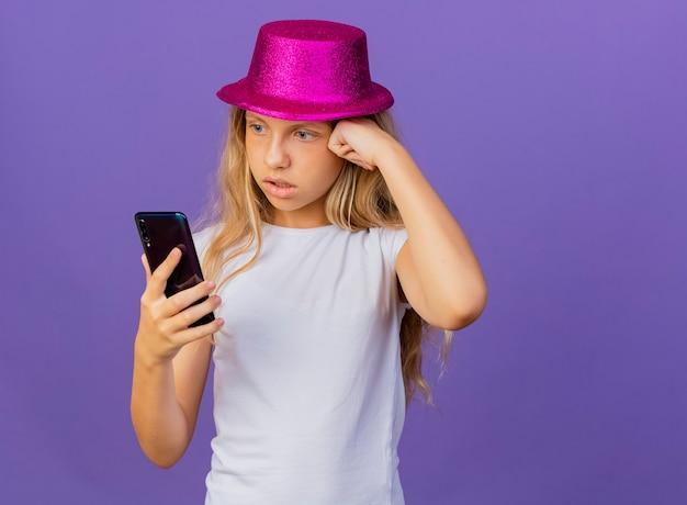 Bambina graziosa in cappello di festa utilizza lo smartphone cercando confuso e molto ansioso, concetto di festa di compleanno in piedi su sfondo viola