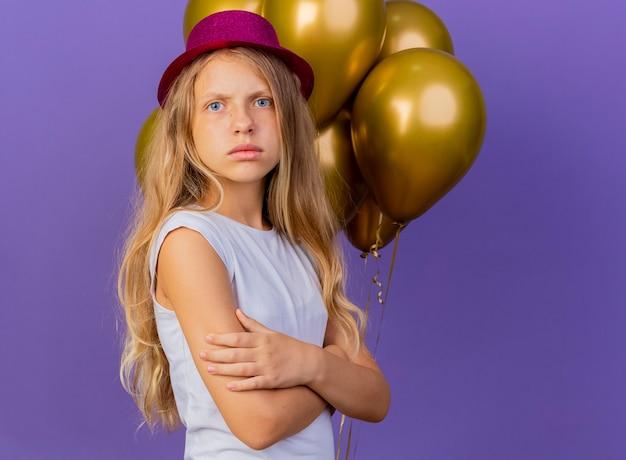 Bambina graziosa in cappello di festa con il mazzo di palloncini con la faccia seria