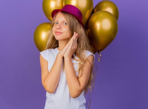 Graziosa bambina in holiday hat con mazzetto di baloons holding palme insieme sorridente in attesa di sorpresa, festa di compleanno concetto in piedi su sfondo viola