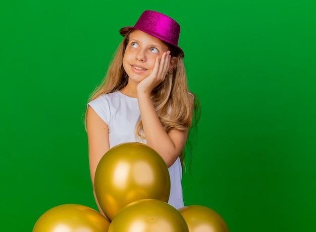 Bambina graziosa in cappello di festa con il mazzo di baloons che osserva da parte sorridere e pensare, concetto della festa di compleanno che sta sopra fondo verde