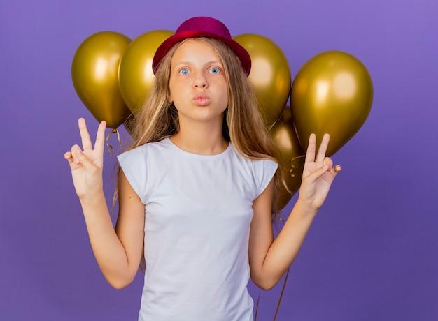 Graziosa bambina in vacanza hat con un mazzo di baloons guardando la telecamera felice e positivo che mostra v-segno, festa di compleanno concetto in piedi su sfondo viola