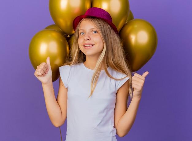 Graziosa bambina in holiday hat con mazzetto di baloons guardando la telecamera sorridente che mostra i pollici in su, festa di compleanno concetto in piedi su sfondo viola