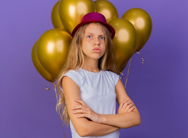 Pretty little girl in holiday hat with bunch of baloons looking at camera with serious face being dissatisfied, birthday party concept standing over purple background