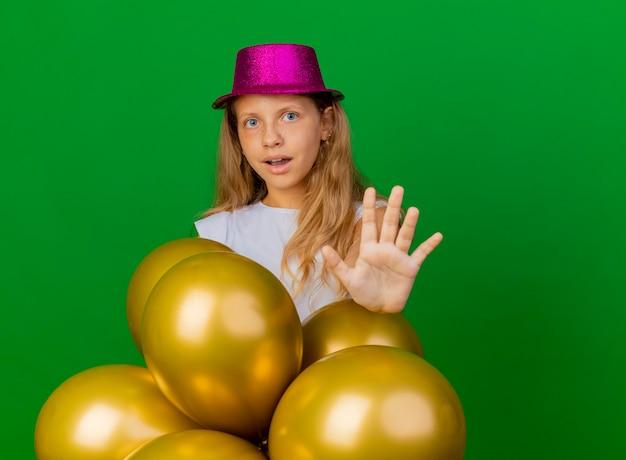 Bambina graziosa in cappello di festa con il mazzo di baloons che fa il fanale di arresto con la mano, concetto della festa di compleanno che sta sopra fondo verde