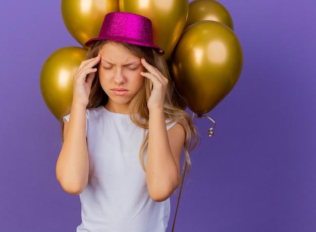 Bambina graziosa in cappello di festa con il mazzo di baloons che tocca le sue tempie che hanno mal di testa, concetto di festa di compleanno in piedi su sfondo viola