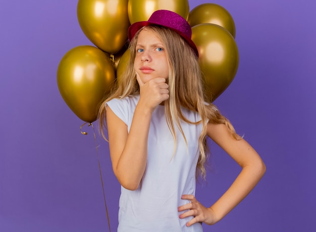 Pretty little girl in holiday hat with bunch of baloons with pensive expression