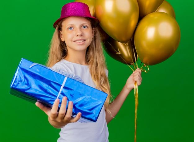 Bambina graziosa in cappello di festa con il mazzo di baloons