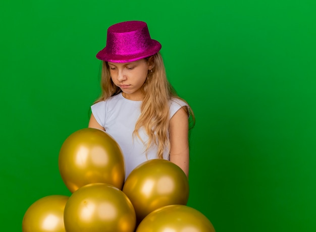 Pretty little girl in holiday hat with bunch of baloons