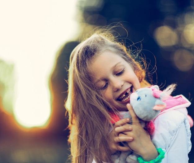 Милая маленькая девочка обнимает любимую мягкую игрушку - кошку для