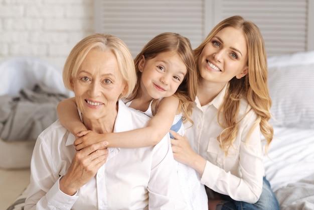 그녀의 어머니가 그녀의 뒤에 앉아있는 동안 그녀의 목에 양손으로 그녀의 우아한 유쾌한 할머니를 안고있는 예쁜 소녀와 그들 모두는 미소로 정면을 바라보고 있습니다.