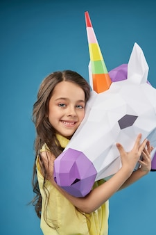 Pretty little girl hugging white 3d unicorn head.