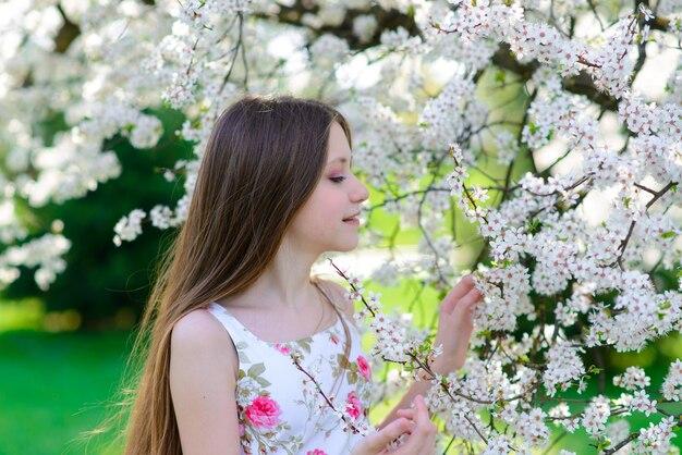 Милая маленькая девочка в цветущем саду яблонь в прекрасный весенний день