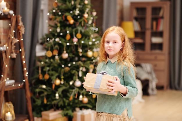 装飾されたモミの木と燃えているろうそくに対してカメラの前に立っている間クリスマスプレゼントとギフトボックスを保持しているカジュアルウェアのかわいい女の子