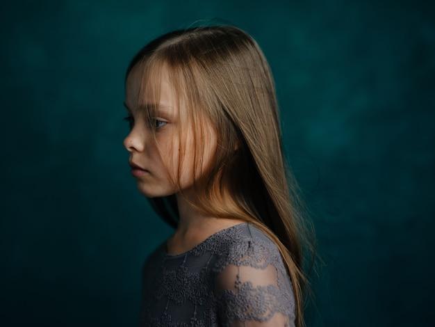 Красивая маленькая девочка в сером платье с распущенными волосами портрет обрезанный вид