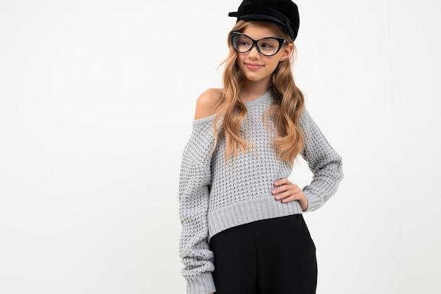 Симпатичная маленькая девочка в серой блузке, кепке и очках улыбается изолированно