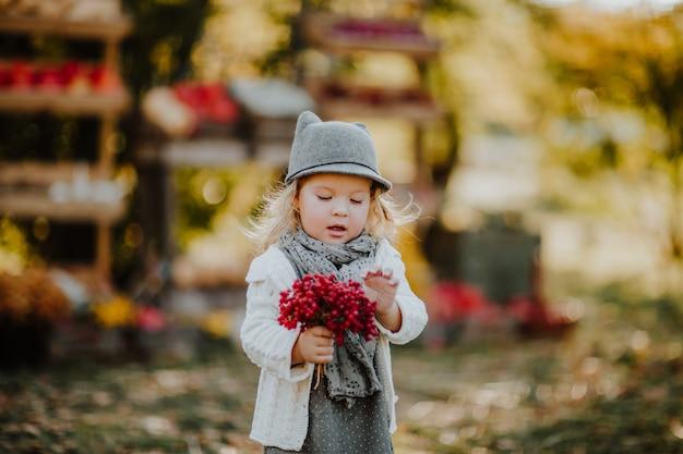 灰色の帽子とスカーフが赤い灰ベリーの束を保持しているかわいい女の子。市場の背景
