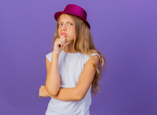 턱 생각에 손으로 얼굴에 잠겨있는 표정으로 카메라를 찾고 휴일 hant에 예쁜 소녀, 보라색 배경 위에 서있는 생일 파티 개념
