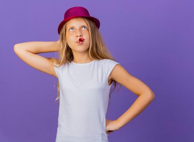 보라색 배경 위에 서 의아해 생일 파티 개념을 찾고 휴가 모자 날리는 휘파람에 예쁜 소녀
